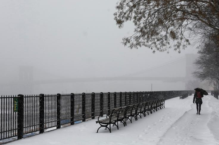 A woman walks with an umbrella along the Brooklyn Promenade during snow fall in New York